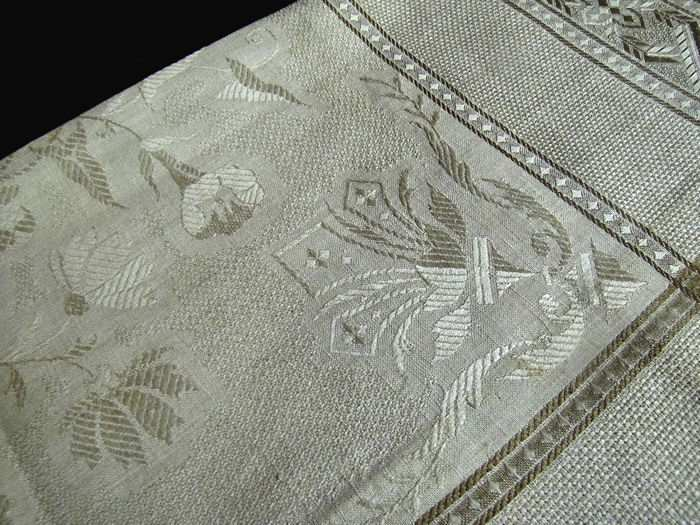 close up vintage damask woven table topper with fringe