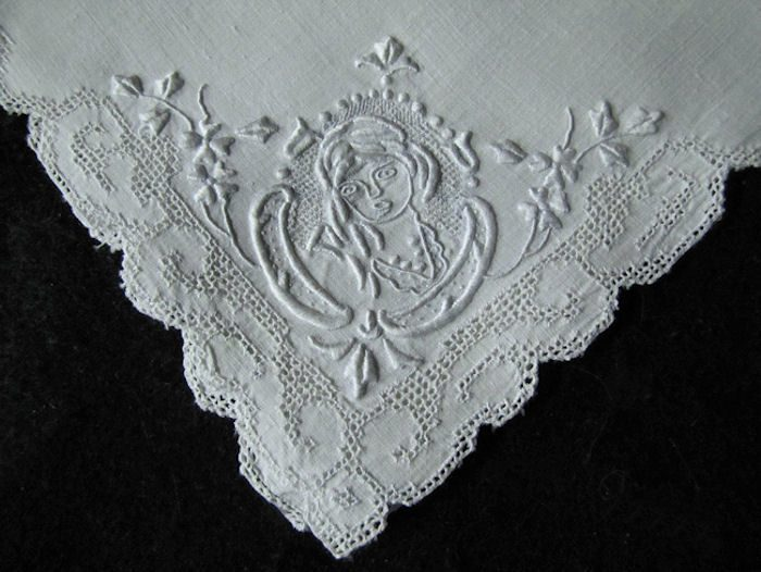 close up Appenzell figural lace on vintage white linen napkins
