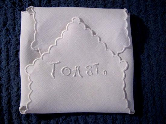 close up vintage handmade white linen roll cover embroidered toast