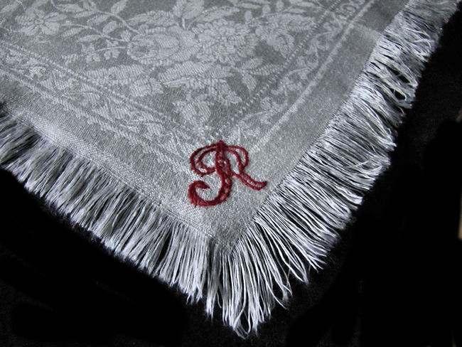 close up monogram R on vintage white linen napkins