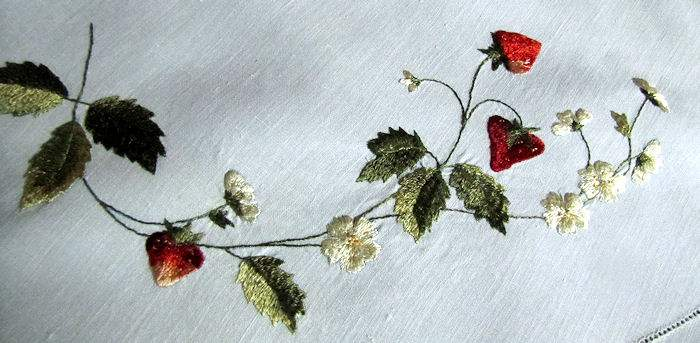 close up vintage antique handmade linen table topper with lace and society silk strawberries