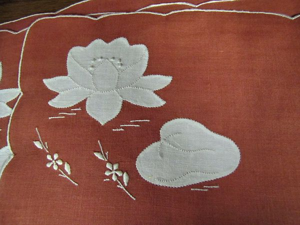 close up vintage red linen placemats with water lilies