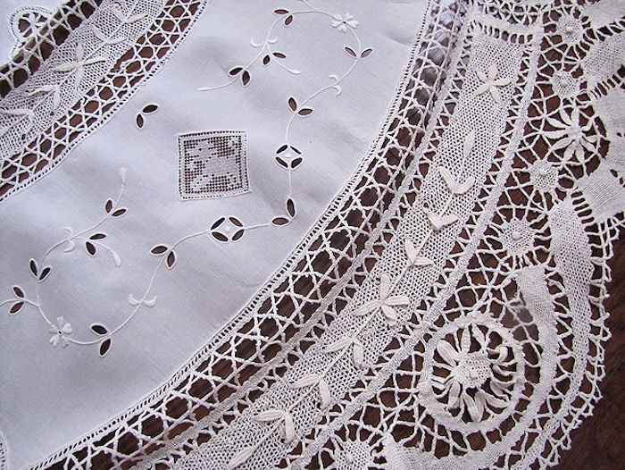 close up vintage antique handmade round tablecloth Cluny and figural lace