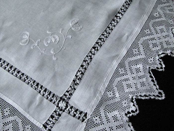 close up vintage antique white linen tablecloth with handmade lace and embroidery