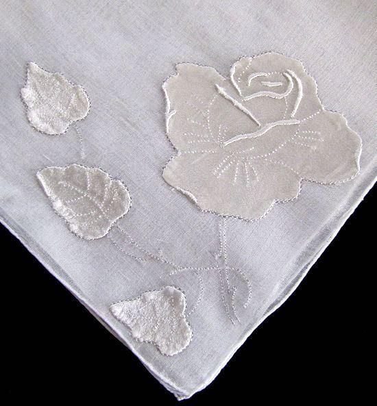 close up of white satin rose on vintage handmade whitework hanky