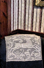 vintage handmade figural lace textile decorates and protects chair back