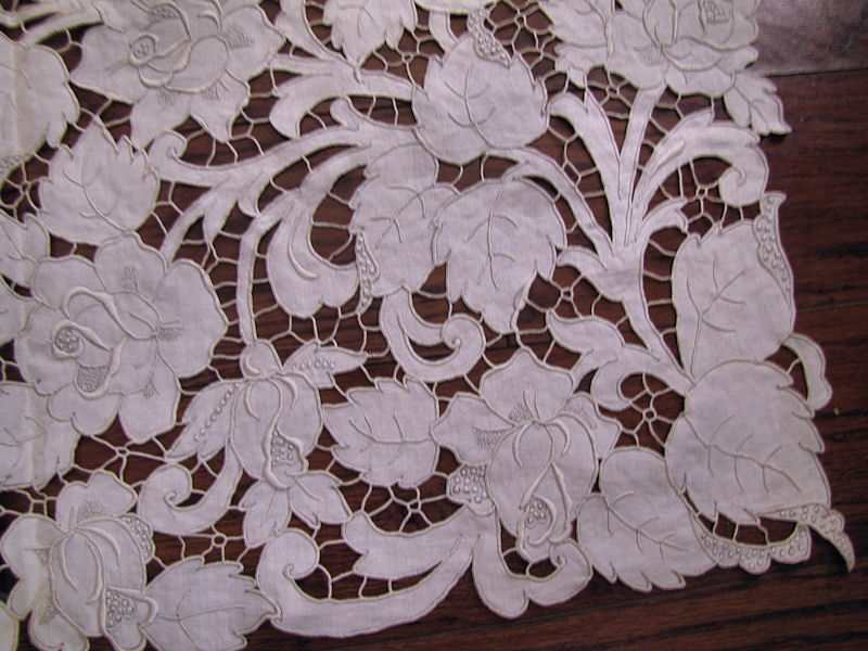 close up vintage antique white linen tablecloth handmade lace and embroidery